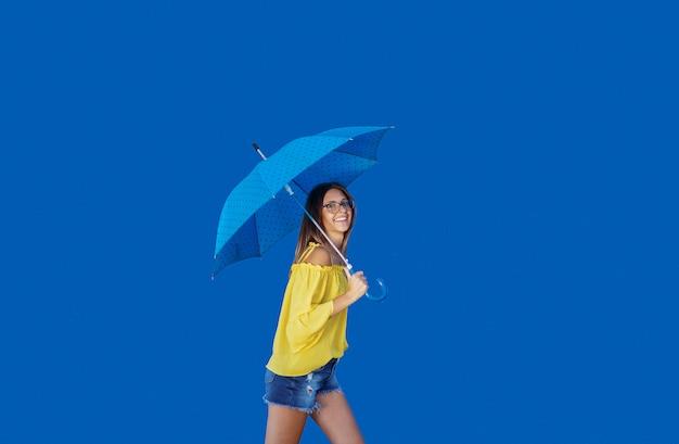 Beautiful smiling caucasian teenage girl in yellow blouse walking with blue umbrella.