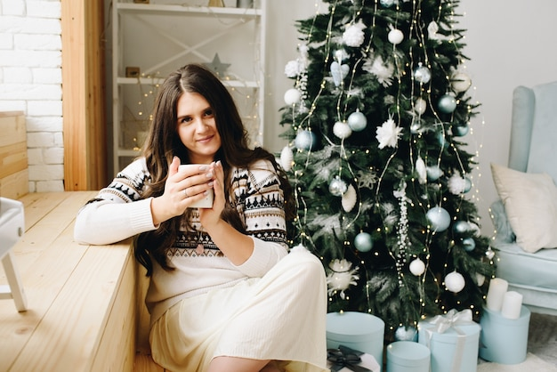 Beautiful smiling caucasian woman with cup sitting near stylish decorated christmas tree