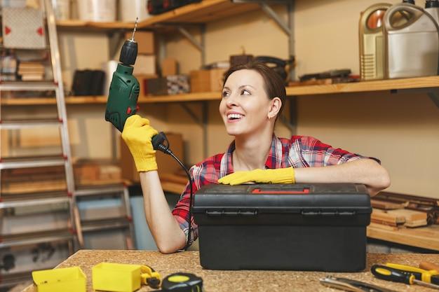 格子縞のシャツ、灰色のtシャツ、木製のテーブルの場所で大工のワークショップで働いている黄色い手袋の美しい笑顔の白人の若い茶色の髪の女性は、ツールボックス、さまざまなツールからパワードリルを取り出しました。