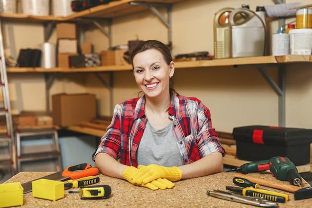 Красивая улыбающаяся кавказская молодая женщина с каштановыми волосами в клетчатой рубашке, серой футболке, желтых перчатках, работающих в столярной мастерской на месте деревянного стола с различными мужскими рабочими инструментами. гендерное равенство.