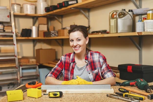 Красивая улыбающаяся кавказская молодая женщина с каштановыми волосами в клетчатой рубашке, серой футболке, желтых перчатках, работающих в столярной мастерской на месте деревянного стола с куском железа и дерева, различными инструментами.
