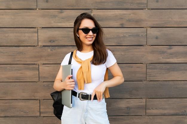 Красивая улыбающаяся очаровательная молодая брюнетка женщина, смотрящая на камеру, держащую компьютерный ноутбук и солнцезащитные очки в белой футболке и голубых джинсах на улице.
