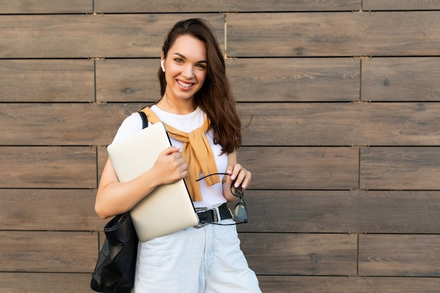 Beautiful smiling charming young brunet woman looking at camera holding computer laptop and sunglasses in white t-shirt and light blue jeans in the street.