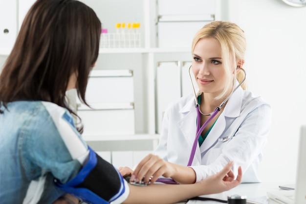 美しい笑顔の陽気な女性医学博士が患者に血圧を測定します。医療とヘルスケアの概念