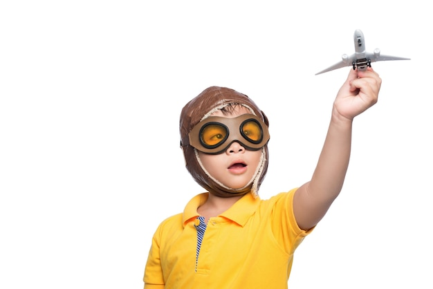 비행기를 가지고 노는 흰색 배경에 헬멧에 아름 다운 웃는 아이 소년.