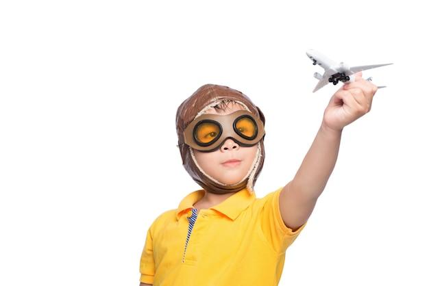 飛行機で遊んで白い背景の上のヘルメットの美しい笑顔の子供の男の子。