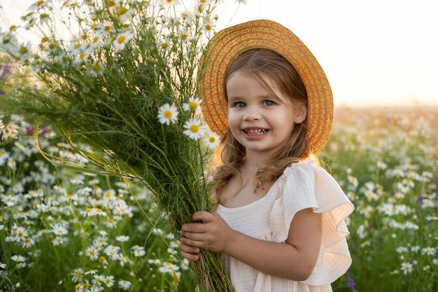 麦わら帽子の美しい笑顔の子供の女の子は、日没時にフィールドカモミールの花束を保持しています。