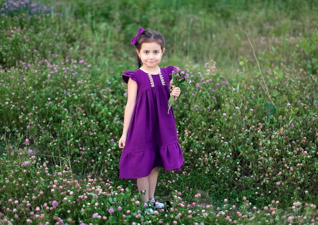 Beautiful smiling child girl in the pink dress on field of red clover in sunset time.