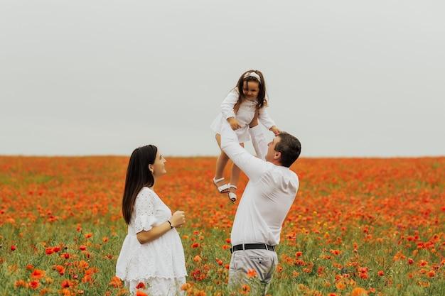 赤いポピーの分野で楽しんでいる母と父と美しい笑顔の子供の女の子
