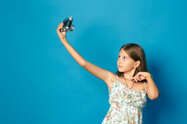Красивый улыбающийся ребенок (девочка) с белыми зубами держит камеру и делает селфи