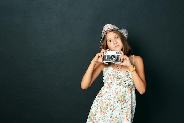 Красивый улыбающийся ребенок (девочка) с белыми зубами, держащий мгновенную камеру