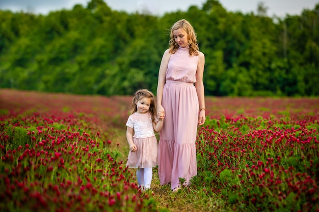 Beautiful smiling child girl with young mother in family look in field of clover flowers in sunset time