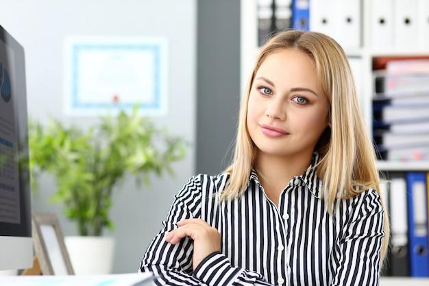 Beautiful smiling clerk sitting at working table