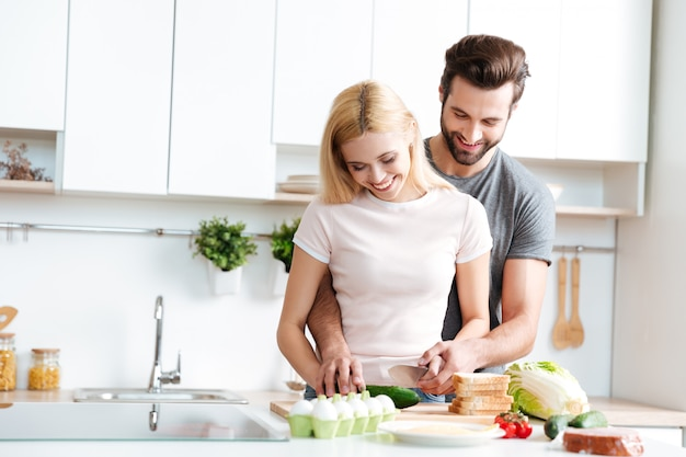 Красивые улыбающиеся пары вместе готовить в современной кухне