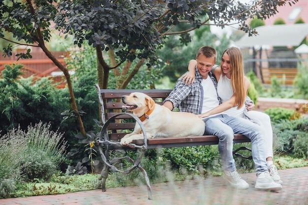 Красивая улыбающаяся пара, сидящая на скамейке со своей собакой в парке