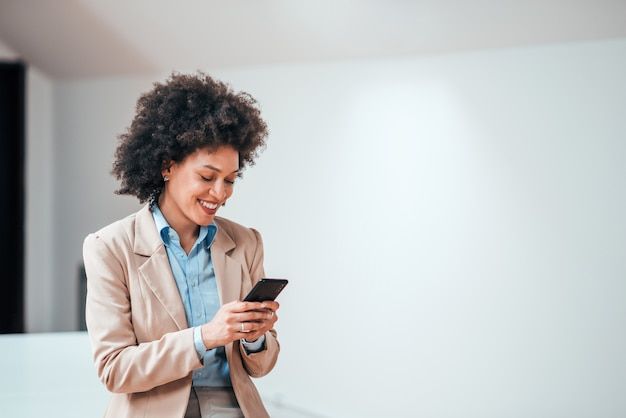 Beautiful smiling curly-haired businesswoman using smarphone indoors, copy space.