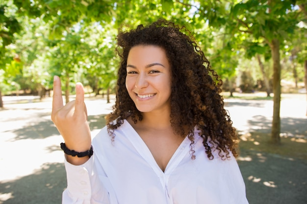 Beautiful smiling curly woman showing devil horns sign