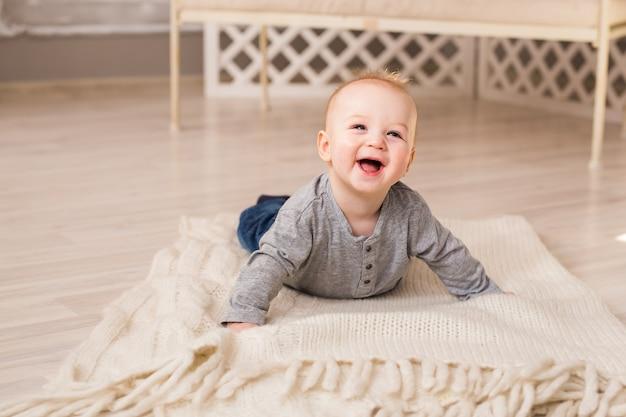 Красивый улыбающийся милый ребенок. смеющийся мальчик лежал на животе у себя дома.