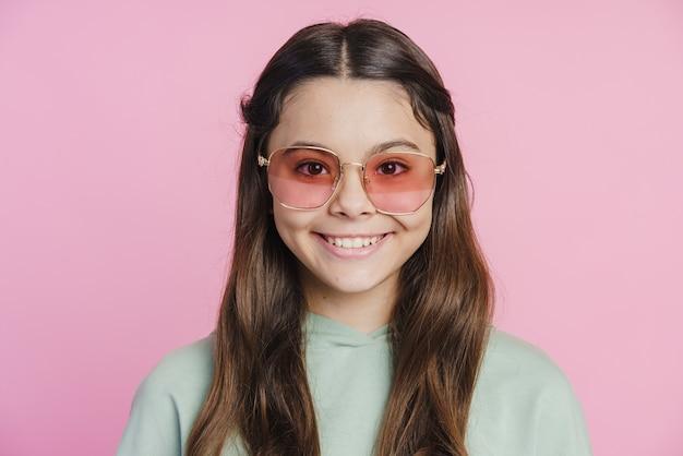 Красивая, улыбающаяся милая девушка улыбается на розовом фоне. на девушке солнцезащитные очки