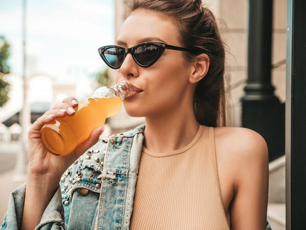 通りでポーズをとる夏のヒップスタージーンズジャケット服の美しい笑顔のかわいいモデル