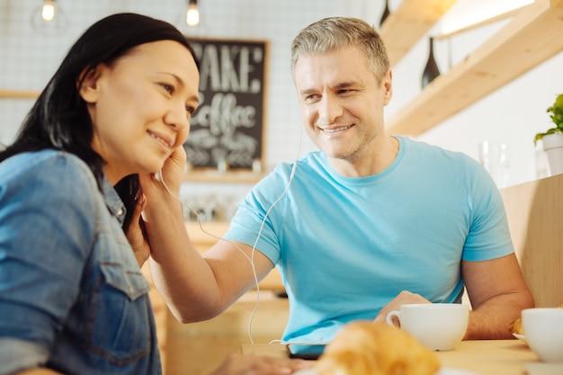 Красивая улыбающаяся темноволосая женщина и красивый бдительный блондин сидят за столом в кафе и слушают музыку и пьют кофе