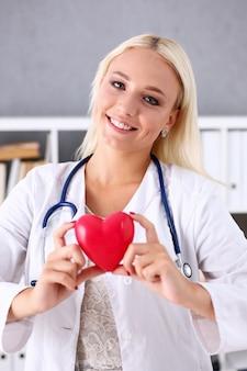 美しい笑顔の医者は腕の中で赤いハートを保持します。