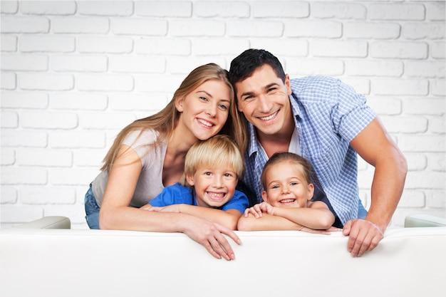 ソファの上の部屋で美しい笑顔の家族