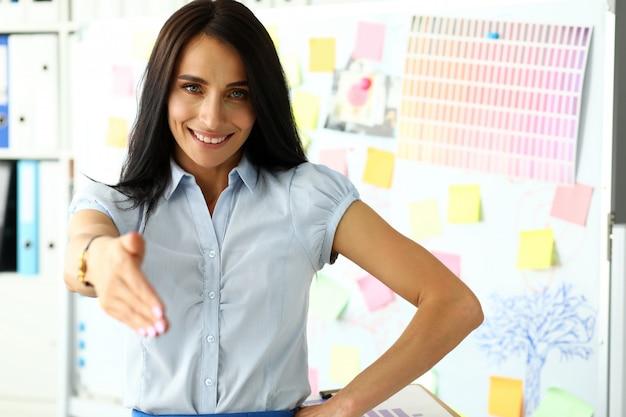 Красивая улыбающаяся женщина-клерк, предлагающая руку клиенту