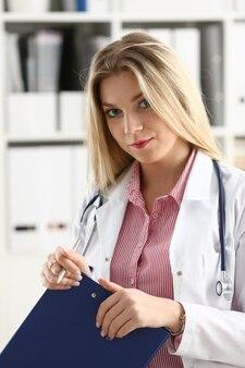 美しい笑顔の女性医師はクリップボードを保持します