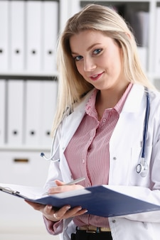 Beautiful smiling female doctor hold clipboard
