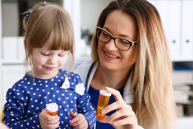 美しい笑顔の女性医師が腕の錠剤で保持します。