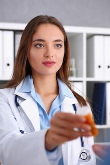 Красивая улыбающаяся женщина-врач держит в руках