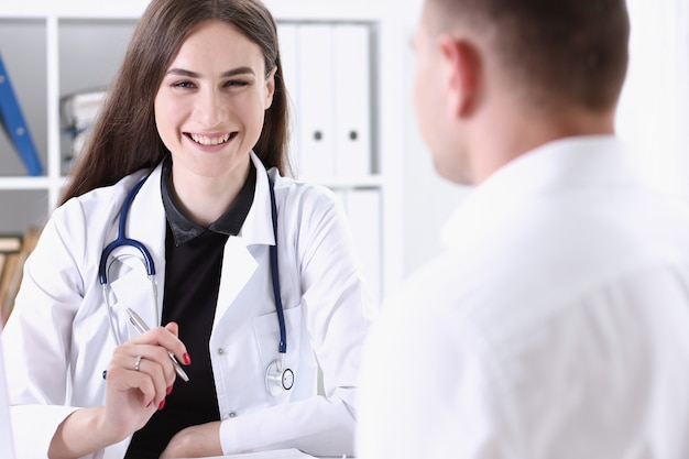 Beautiful smiling female doctor hold silver pen