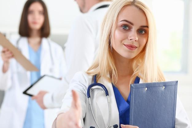 Красивая улыбающаяся женщина-врач показывает нормально