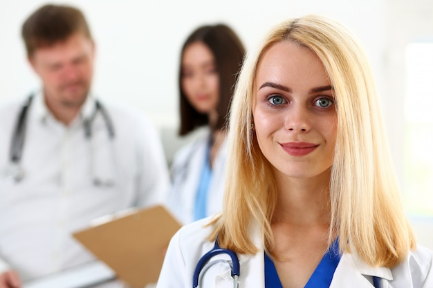 Beautiful smiling female doctor stand in office