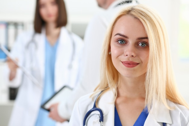 Beautiful smiling female doctor stands in office portrait.