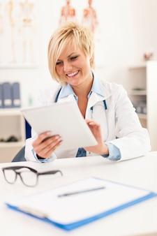 Bello medico femminile sorridente che per mezzo della compressa digitale in ufficio