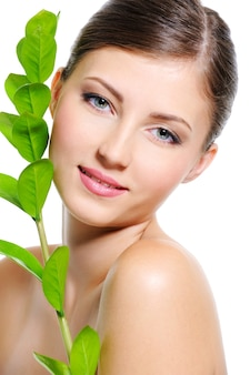 Beautiful smiling female face with a clean healthy skin and plant near her body