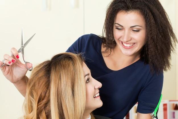 はさみを持ってクライアントを見ている美しい笑顔の女性美容師。健康な髪、最新のヘアファッショントレンド、ヘアカットスタイルの変更、スプリットエンドの短縮、楽器店のコンセプト