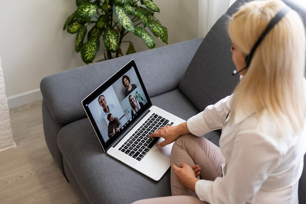 온라인 교육 서비스를 사용하는 아름다운 웃는 여학생. 노트북 디스플레이를 보고 있는 젊은 여성이 교육 과정을 보고 헤드폰으로 듣고 있습니다. 현대 연구 기술 개념