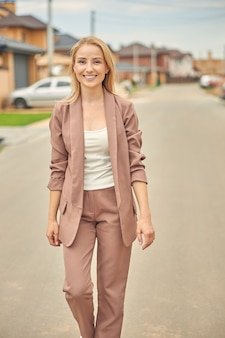 Beautiful smiling female in a trendy suit walking along the street in a residential area