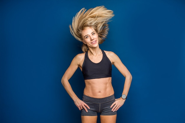 Beautiful smiling fit young woman in sport bra with flowing hair. dance, gym, slim concept
