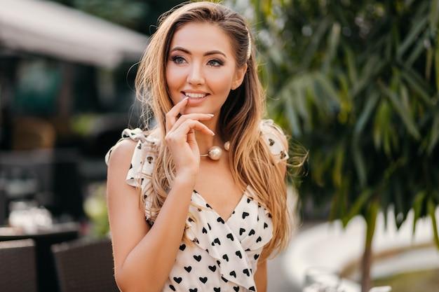 Bella donna sorridente flirtare vestita in abito stampato bianco in stile romantico in posa in street cafe in giornata di sole