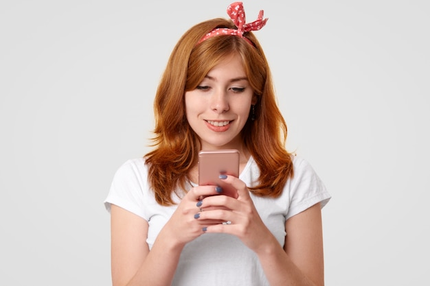 Beautiful smiling ginger female with charming smile, uses modern mobile phone, messages with friends