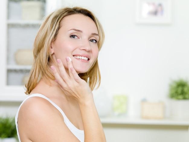 Bella ragazza sorridente che applica crema sul viso