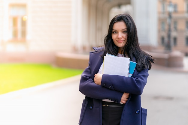 Beautiful smiling girl brunette student holding notebooks and textbooks, stands at university