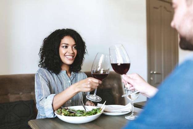 레스토랑에서 친구와 함께 레드 와인을 마시는 아름 다운 웃는 소녀. 샐러드를 먹고 카페에서 와인을 마시는 꽤 아프리카 계 미국인 여자