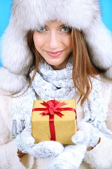 Beautiful smiling girl in hat with gift on blue background