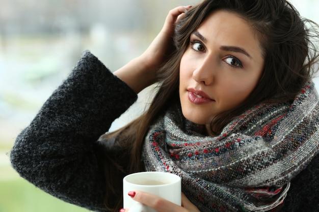 腕のカップの肖像画で美しい微笑の女の子ホールド