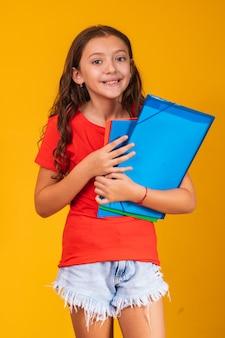 学校に行く本を持っている美しい笑顔の女の子。肖像画、孤立した黄色の背景、子供時代を閉じます。本を抱き締める子供。ライフスタイル、興味、趣味、自由時間、自由時間